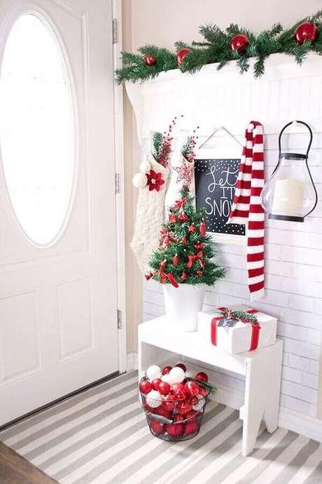 21. Hall de entrada branco decorado com festão de Natal decorado com bolas vermelhas – Foto: Archidea