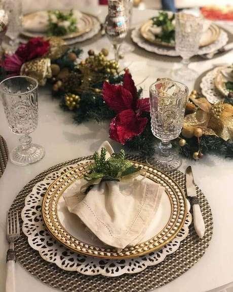 23. Festão de Natal decorado com flores vermelhas e detalhes em dourado para mesa de natal – Foto: Pinterest