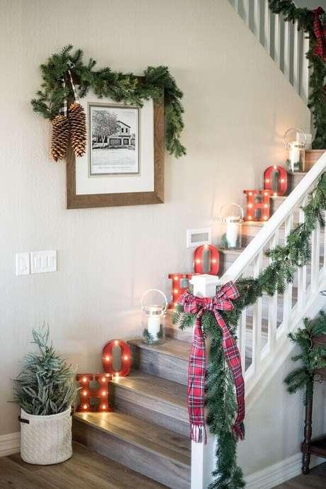 24. Decoração de escada com luminárias de letras e enfeites de Natal com festão e laço xadrez – Foto: Elle Decor