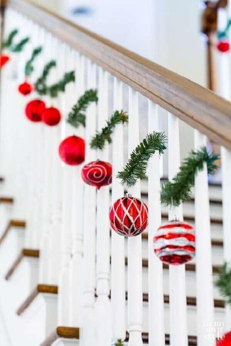 33. Escada decorada com enfeites de Natal com festão e bolas vermelhas – Foto: In My Own Style