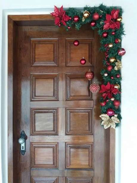 36. Festão de Natal verde decorado com flores e bolas douradas e vermelhas para porta – Foto: Muito Chique