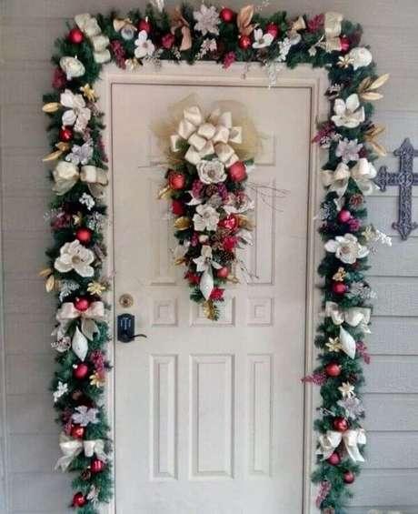 38. Porta de entrada decorada com bolas e flores para festão de Natal – Foto: Pinterest