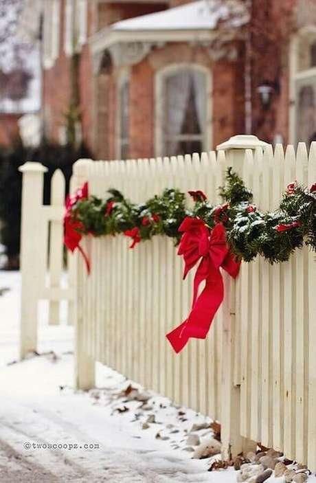 39. Cerca branca de casa decorada com festão de Natal verde decorado com laços vermelhos – Foto: Trend4Homy