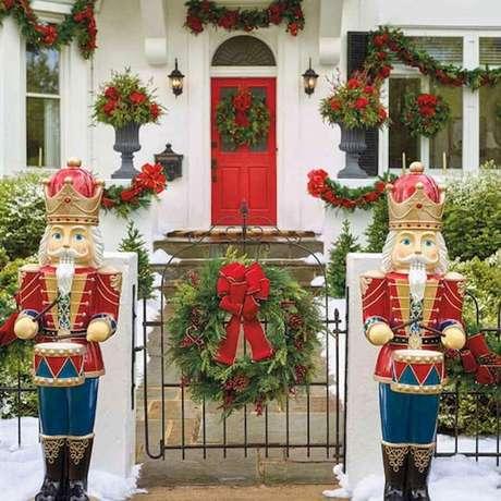 41. Linda fachada de casa decorada com vários enfeites de Natal com festão e flores vermelhas – Foto: Pinterest