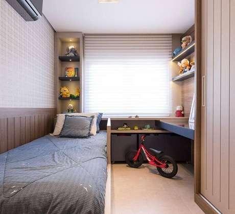 34. Decoração de quarto de solteiro pequeno planejado com iluminação nas prateleiras – Foto: Braccini + Lima Arquitetura