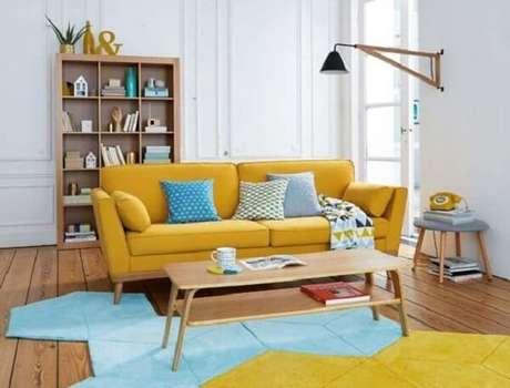 20. A mesa de centro retrô em madeira segue quase o mesmo comprimento que o sofá amarelo. Fonte: Notre Loft