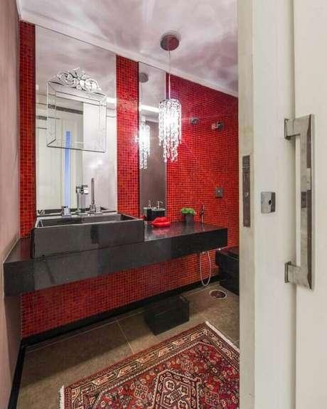 15. Bancada planejada preta para decoração de banheiro com pastilha vermelha e lustre pendente de cristal – Foto: Pinterest