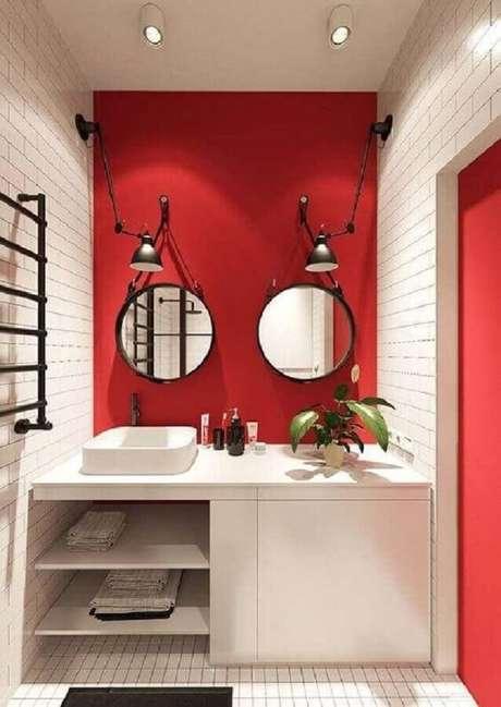 18. Banheiro vermelho e branco decorado com luminária articulada e espelho adnet preto – Foto: Apartment Therapy