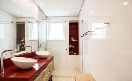 24. Banheiro vermelho e branco decorado com gabinete de madeira – Foto: L2 Arquitetura