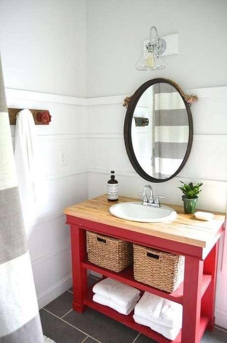 59. Decoração de banheiro vermelho e branco simples com bancada de madeira e espelho redondo – Foto: Planeta Design