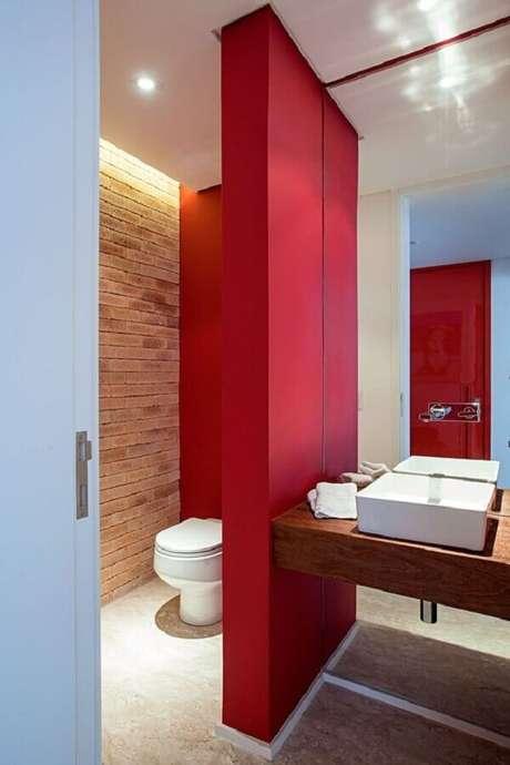 60. Parede de tijolinho e bancada de madeira para decoração de banheiro vermelho – Foto: Casa de Valentina