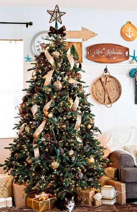 36- O pinheiro de natal tem laços e duas fitas que percorrem os galhos. Fonte: A casa eh sua