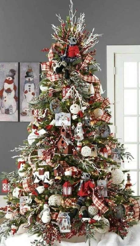 37- Atrás do pinheiro de natal os quadros de boneco de neve complementam a decoração da sala. Fonte: Pinterest