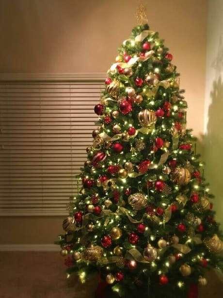 38- O pinheiro de natal foi decorado com bolas vermelhas e douradas. Fonte: kristine in between