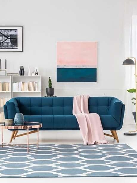 19. Sofá azul, manta rosa e mesa de centro retrô redonda com acabamento delicado decoram a sala. Fonte: New Home Design