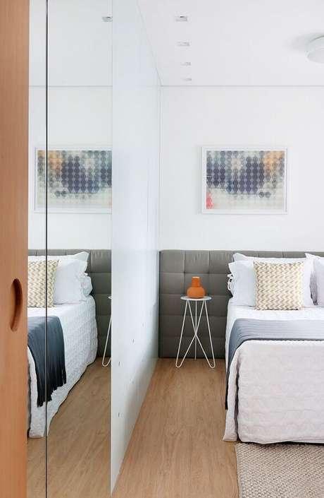 49. Decoração de quarto de casal branco com cabeceira cinza estofada e mesa de cabeceira pequena – Foto: Arquitetura & Construção