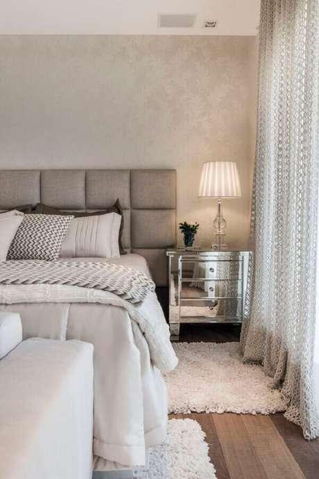 5. Decoração de quarto de casal sofisticado com criado mudo espelhado e cabeceira estofada cinza – Foto: Archilovers