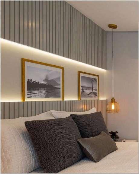 30. Decoração de quarto com cabeceira cinza de madeira e luminária pendente aramada – Foto: Jeito de Casa