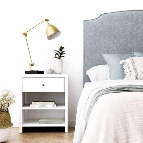 23. Decoração clean para quarto com luminária articulada cobre e cabeceira estofada cinza – Foto: Kenay Home
