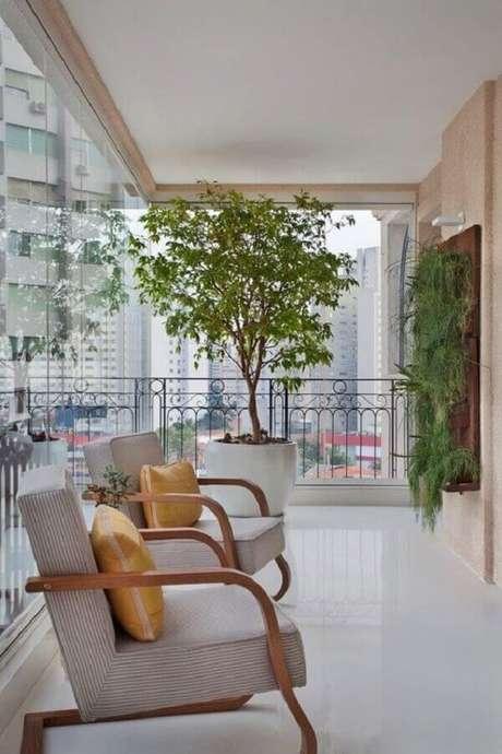 10. Decoração com poltronas de madeira e plantas para varanda de apartamento – Foto: Jeito de Casa