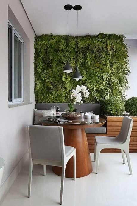 15. Plantas para varanda cinza moderna decorada com mesa redonda de madeira e jardim vertical – Foto: Mariana Orsi