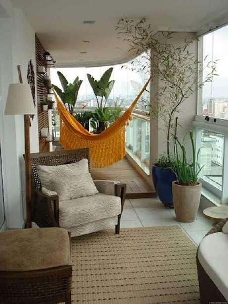 32. Decoração com rede amarela e vasos de plantas para varanda de apartamento – Foto: Histórias de Casa