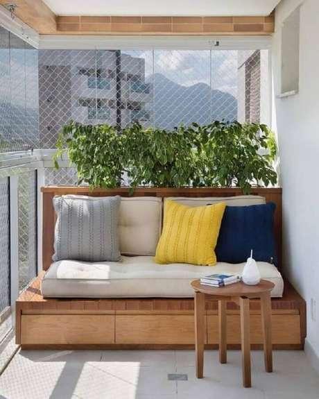 33. Plantas para varanda com sol decorada com banco de madeira e almofadas coloridas – Foto: Simples Decoração