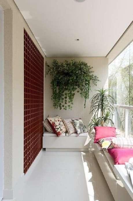 34. Decoração simples com plantas para varanda e bancos brancos com almofadas coloridas – Foto: Arquitrecos