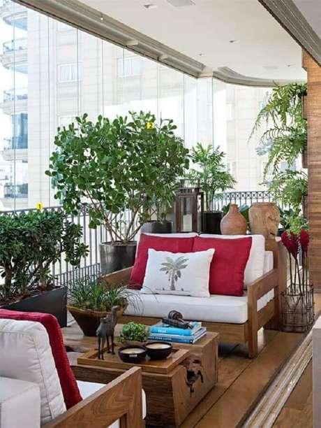 35. Decoração com vasos de plantas para varanda de apartamento confortável decorada com móveis de madeira – Foto: Casa de Valentina