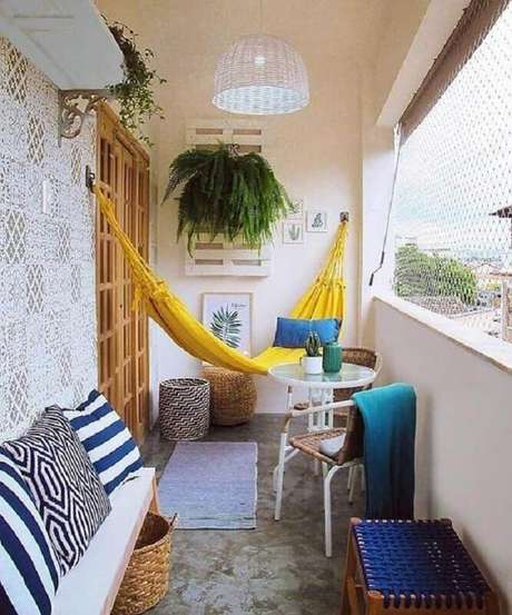43. Decoração com rede amarela e plantas para varanda com sombra – Foto: Jeito de Casa