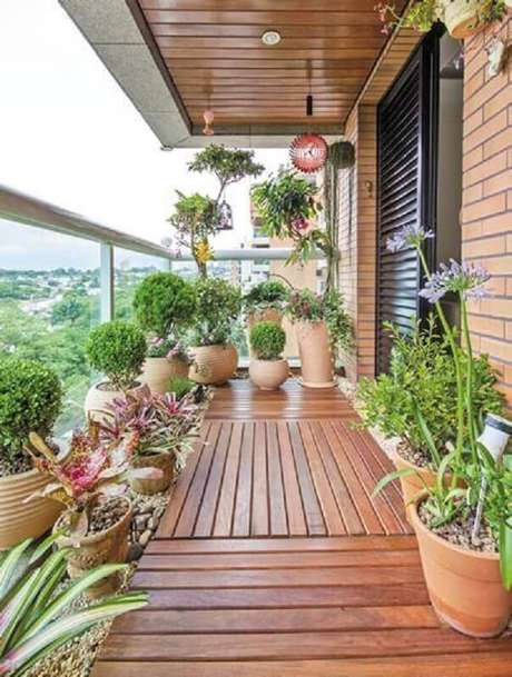 47. Decoração simples com vasos de plantas para varanda de madeira – Foto: Jeito de Casa