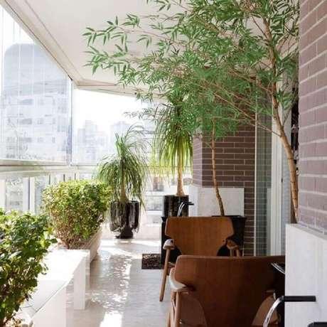 49. Vasos de plantas para varanda de apartamento com poltronas de madeira – Foto: Pinterest