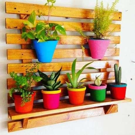 21. Vasos coloridos decoram a prateleira de pallet para plantas. Fonte: Sertão Atelier Decoração
