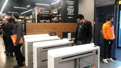 Consumidores entram em uma loja Amazon Go através de um aplicativo em seus smartphones