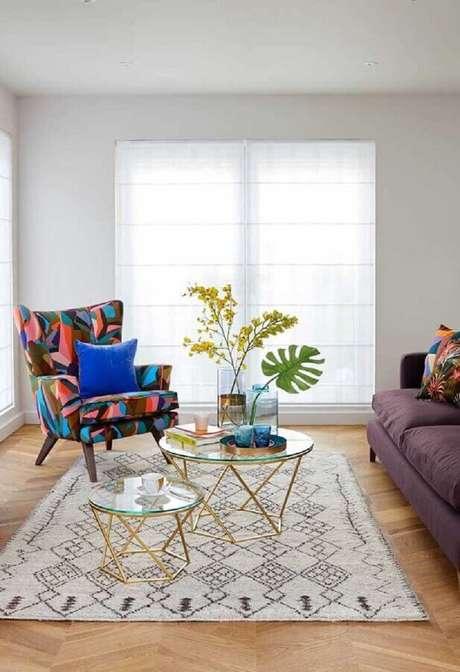 15. Sala clean decorada com mesa de centro de vidro e poltrona colorida – Foto: Casa de Valentina
