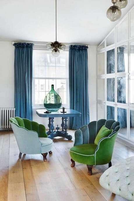 19. Sala decorada com poltronas coloridas em tons de verde e cortina azul – Foto: House & Garden