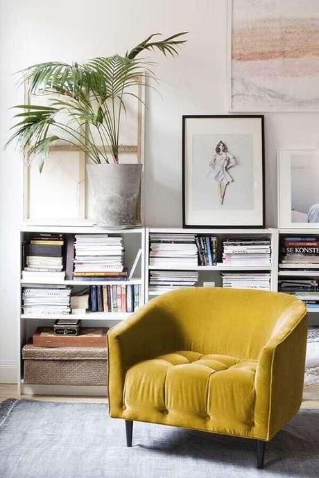36. Poltrona colorida amarela para decoração de sala branca com estante baixa de livros – Foto: Planeta Design