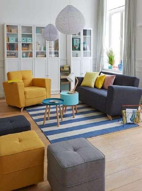 8. Poltrona colorida amarela para sala decorada com sofá cinza e tapete listrado – Foto: Pinterest