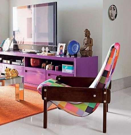 7. Poltrona colorida de madeira para sala descontraída decorada com tapete laranja e rack roxo – Foto: Jeito de Casa