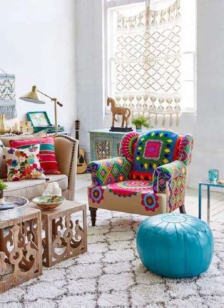 38. Decoração de sala simples com puff redondo azul e poltrona colorida – Foto: HomeGoods