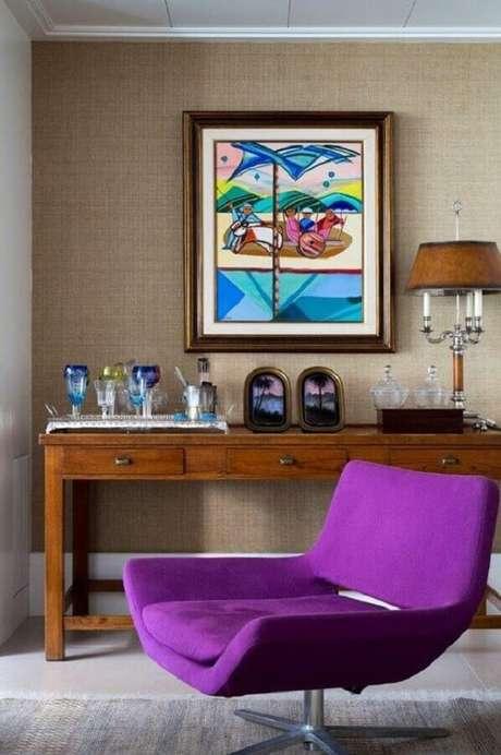 41. Sala decorada com aparador de madeira e poltrona colorida roxa com design moderno – Foto: Histórias de Casa