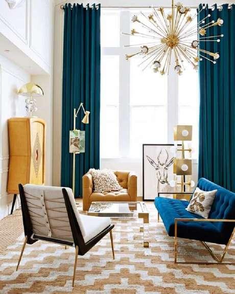 43. Poltrona para sala colorida decorada com lustre pendente moderno e sofá azul – Foto: The Fashion Hall