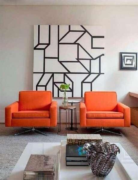 46. Poltronas coloridas na cor laranja para sala moderna decorada com quadro grande – Foto: Pinterest