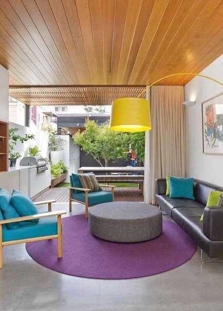 48. Poltronas coloridas para sala moderna decorada com sofá cinza e tapete roxo redondo – Foto: Pinterest
