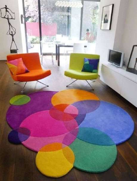 50. Poltronas decorativas coloridas para sala decorada com rack branco e tapete moderno colorido – Foto: Iaza