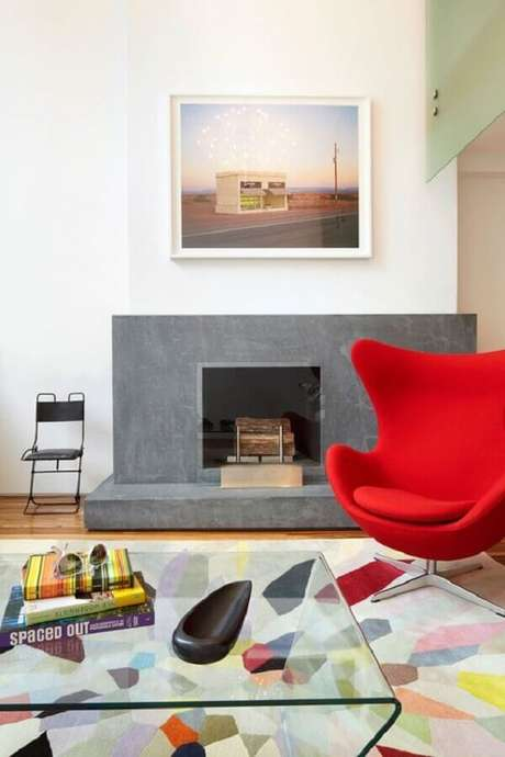 58. Sala com lareira decorada com tapete e poltrona colorida confortável – Foto: One Kindesign