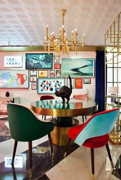 60. Sala de jantar decorada com lustre pendente moderno e poltronas coloridas diferentes – Foto: Moanne