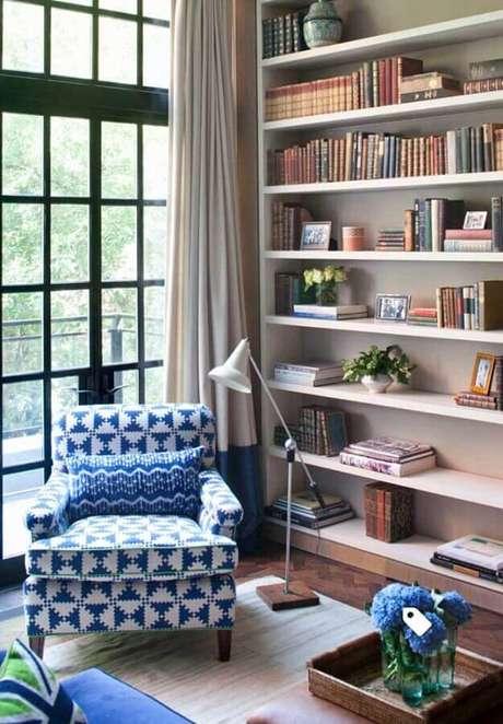 61. Sala decorada com estante planejada e poltrona colorida azul e branca – Foto: Pinterest