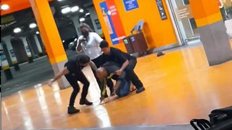 Imagem de agressão no Carrefour, com três funcionários ao redor de homem; caso está sendo comparado com o de George Floyd, sufocado por policiais nos EUA