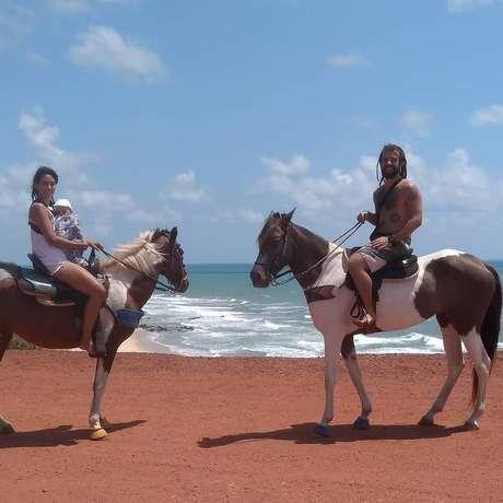 Hugo, Stela e o filho Sol andam a cavalo na praia